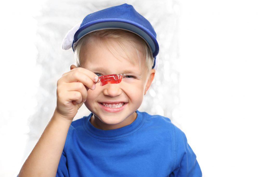 Ortodoncja dziecica, przedszkolak z aparatem ortodontycznym.May chopiec z aparatem ortodontycznym